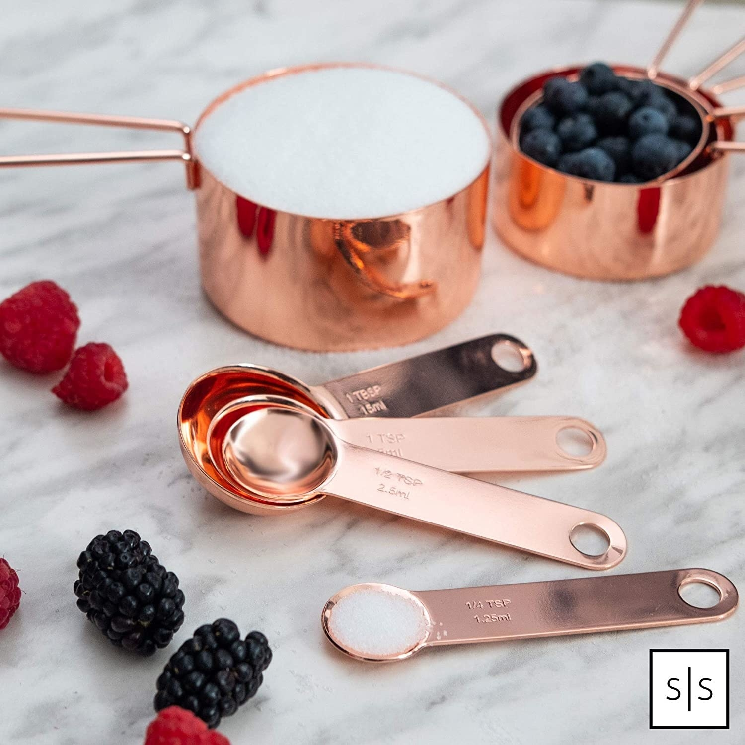 The cup and teaspoon/tablespoons measuring cups in rose gold displayed on a table.