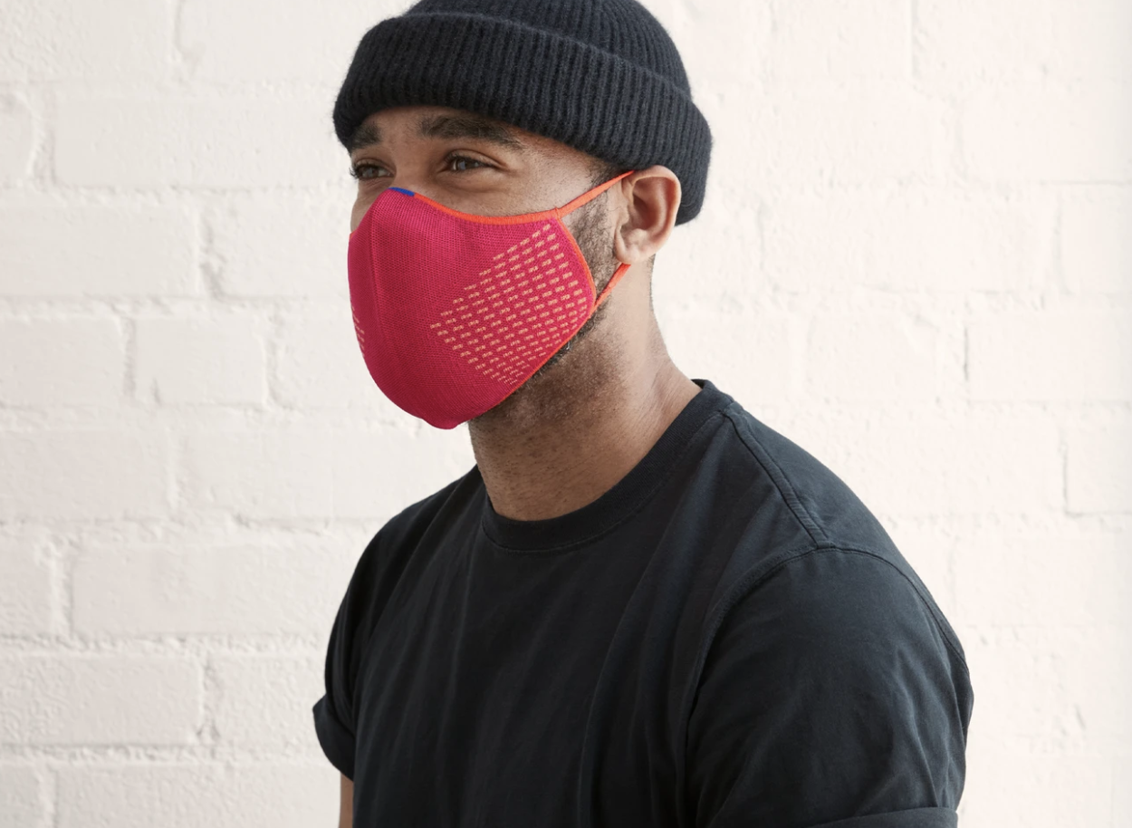 A model in a pink face mask with orange detailing