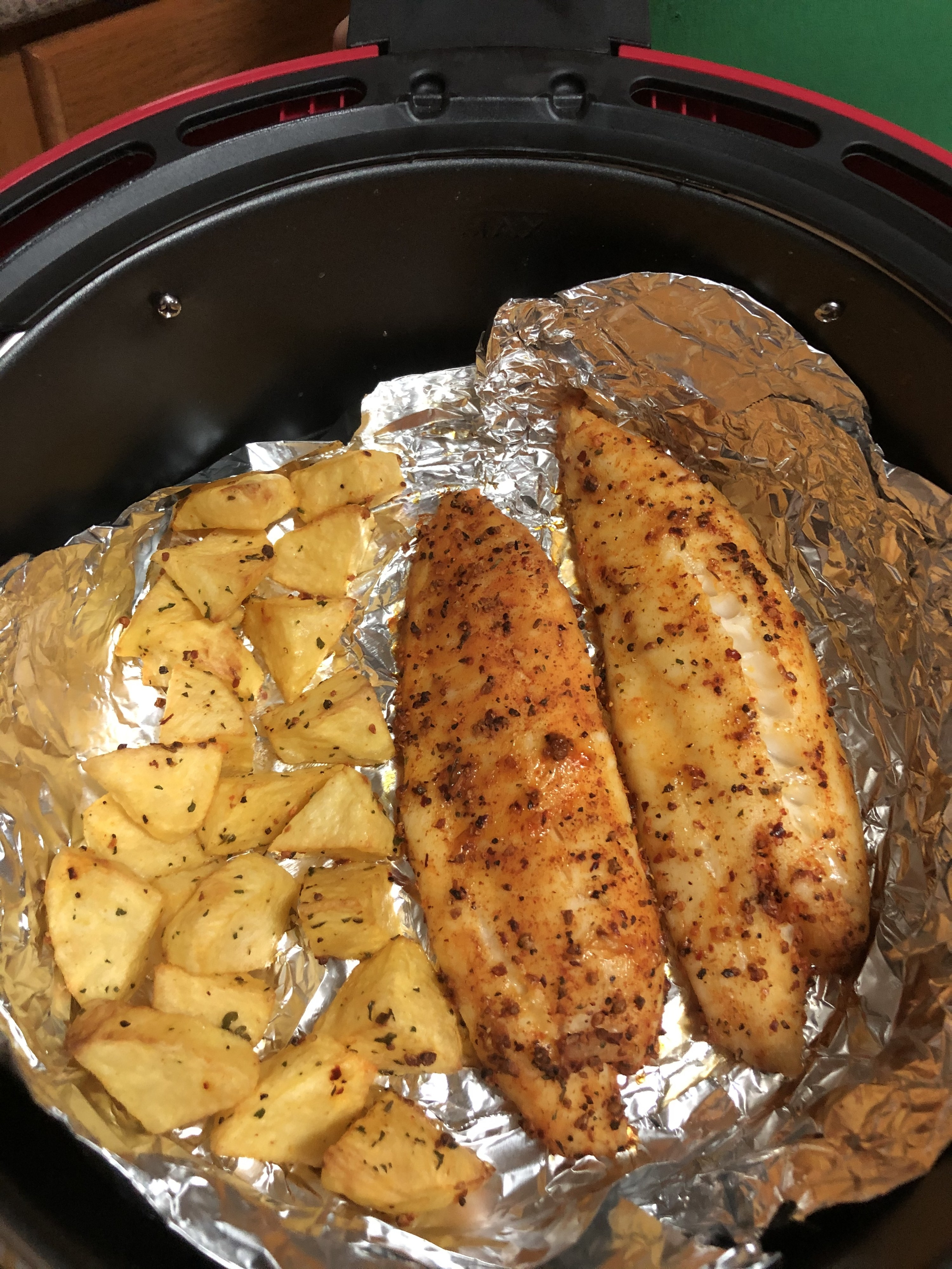 Tilapia fillets and potatoes that have been cooked inside the air fryer