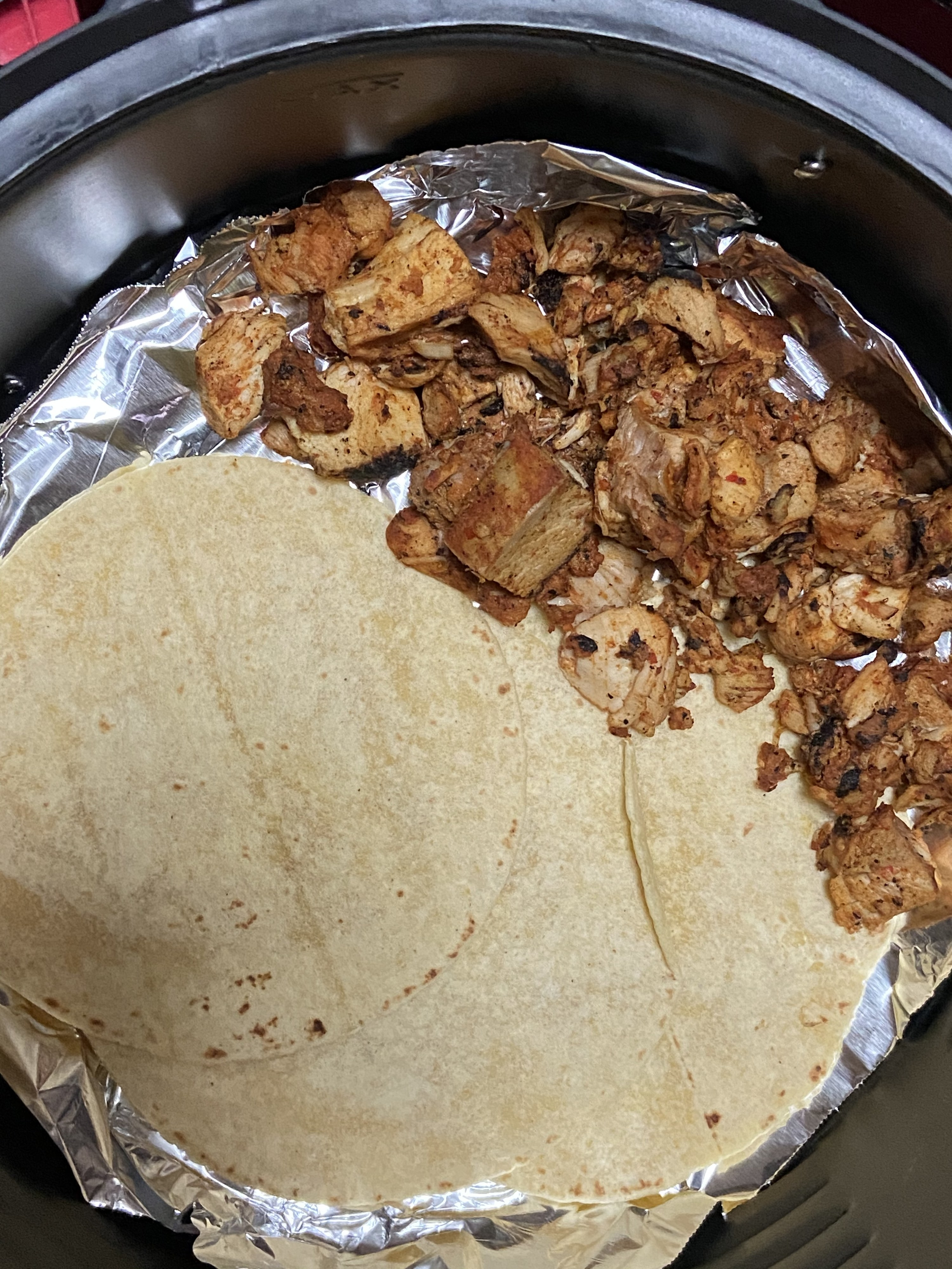 Reheated chicken pieces and tortillas in the air fryer
