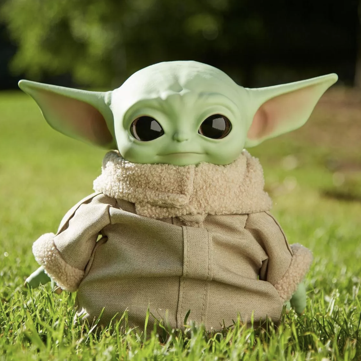 the baby yoda doll in a tan coat outfit
