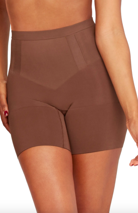A model wearing the Spanx OnCore Mid Thigh Shaper Shorts in chestnut brown.