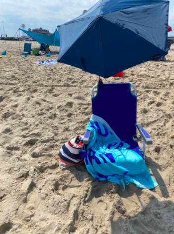 Reviewer uses same adjustable umbrella over their beach chair to get shade from the sun
