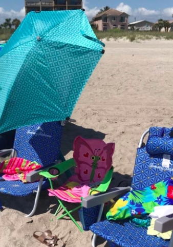 Reviewer places blue-patterned clamp umbrella over blue beach chair