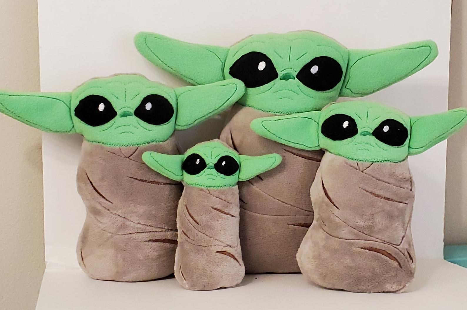 four different sized stuffed baby yoda dolls seemingly swaddled like a baby in a brown blanket