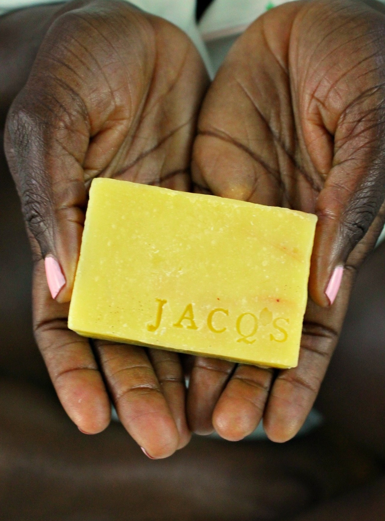 Hands holding up the yellow soap bar