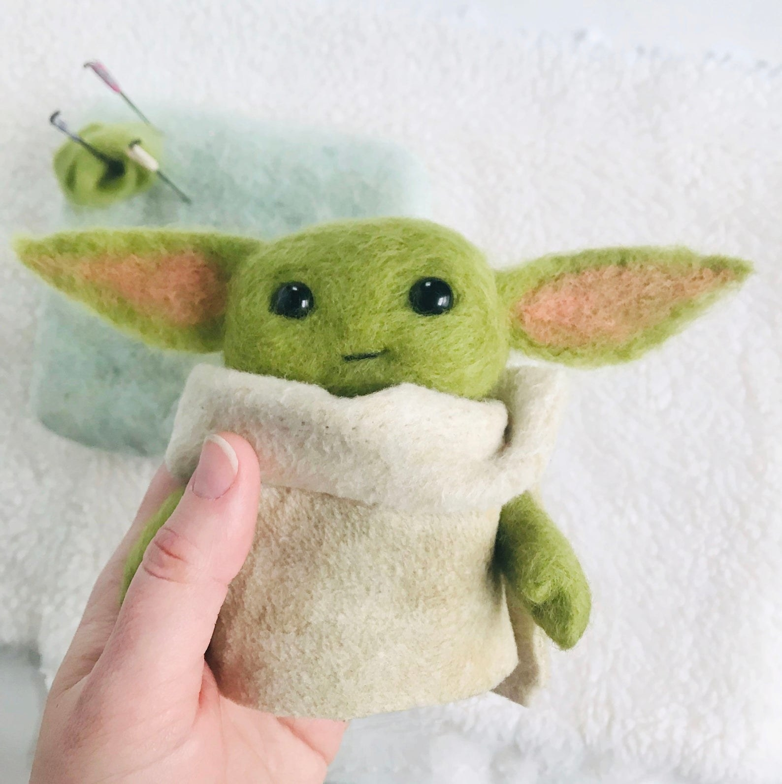 a model holding the woven, soft baby yoda in their hand