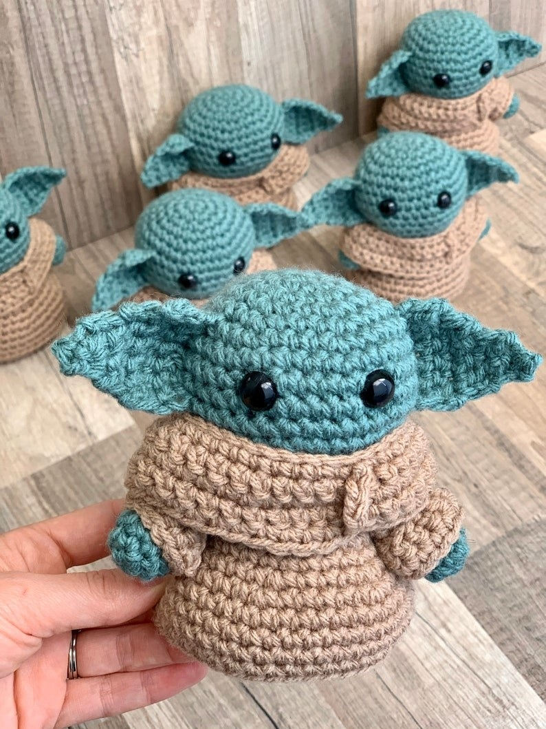 a model holding up the tiny crocheted baby yoda