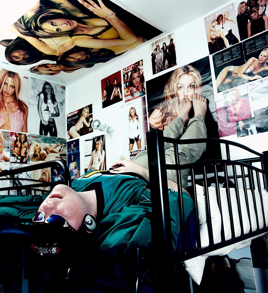 A teenager in his room covered with posters of Britney Spears and Sarah Michelle Geller