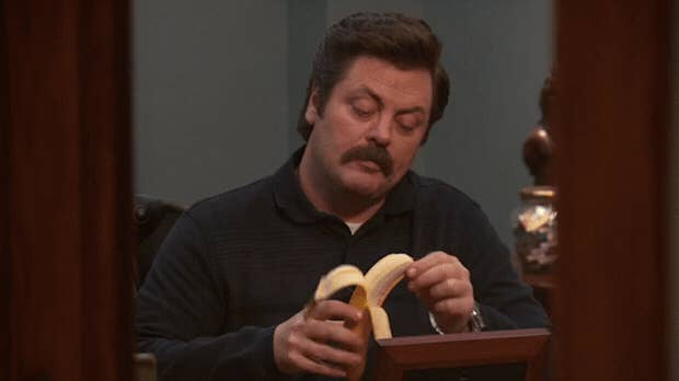 A man with a mustache is unpeeling a banana.