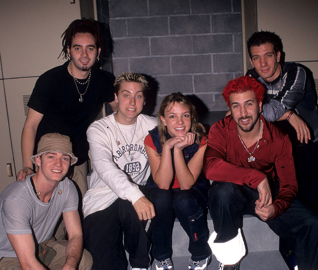 Britney and NSYNC sitting on steps smiling