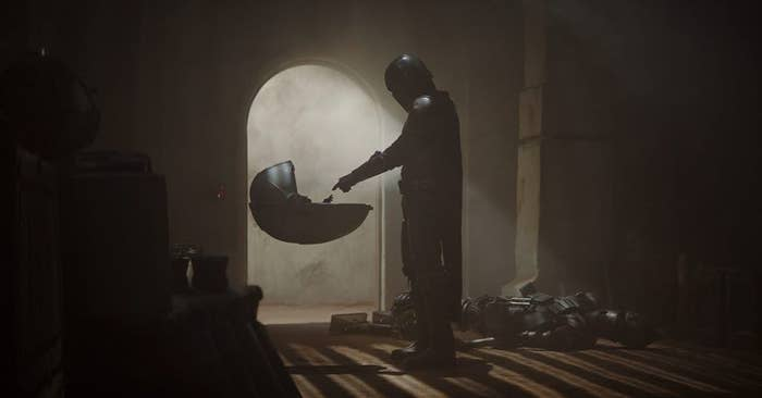 the mandalorian holding his finger out to baby yoda in his pod carriage