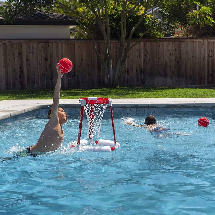 A model about to dunk a ball into the floating hoop in the pool