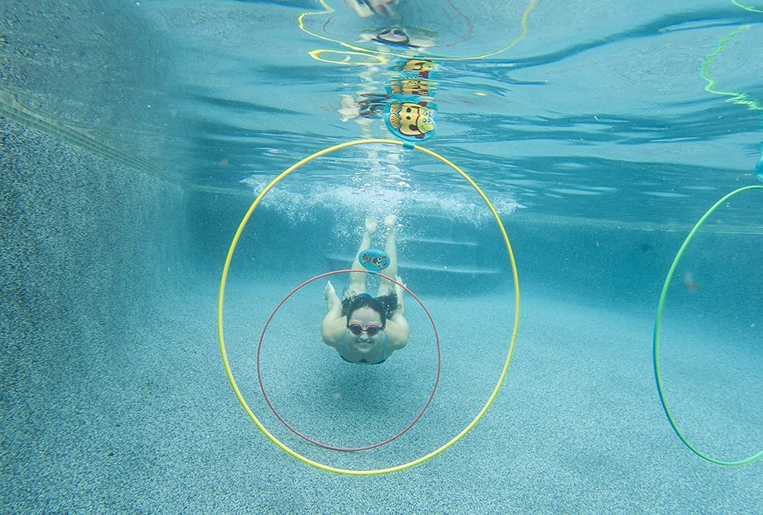 A model underwater about to swim through the rings