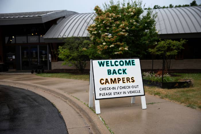 "A sign on a sidewalk outside a building reads ""Welcome back campers, check-in / check-out, please stay in vehicle"""