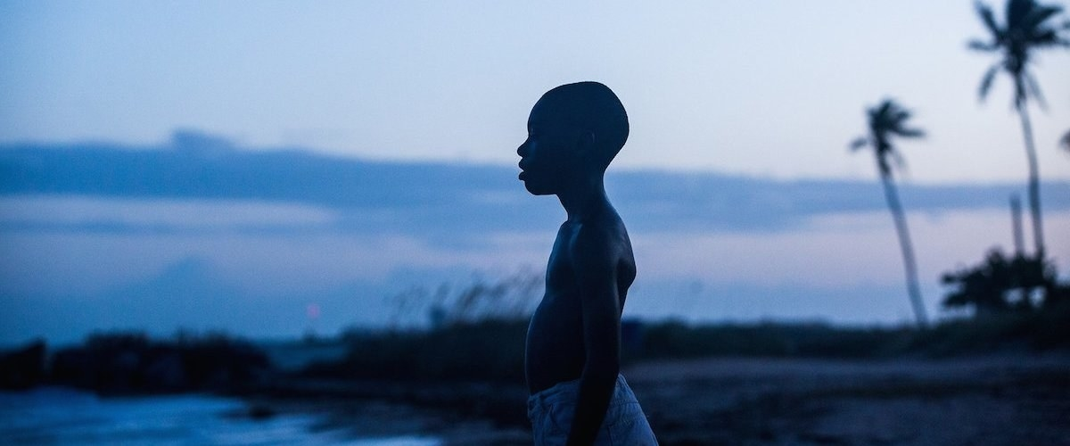 "A young boy in ""Moonlight"" stands on the beach as the sun sets."