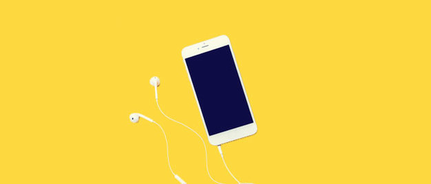A white smart phone with the headphones attached with a yellow background.