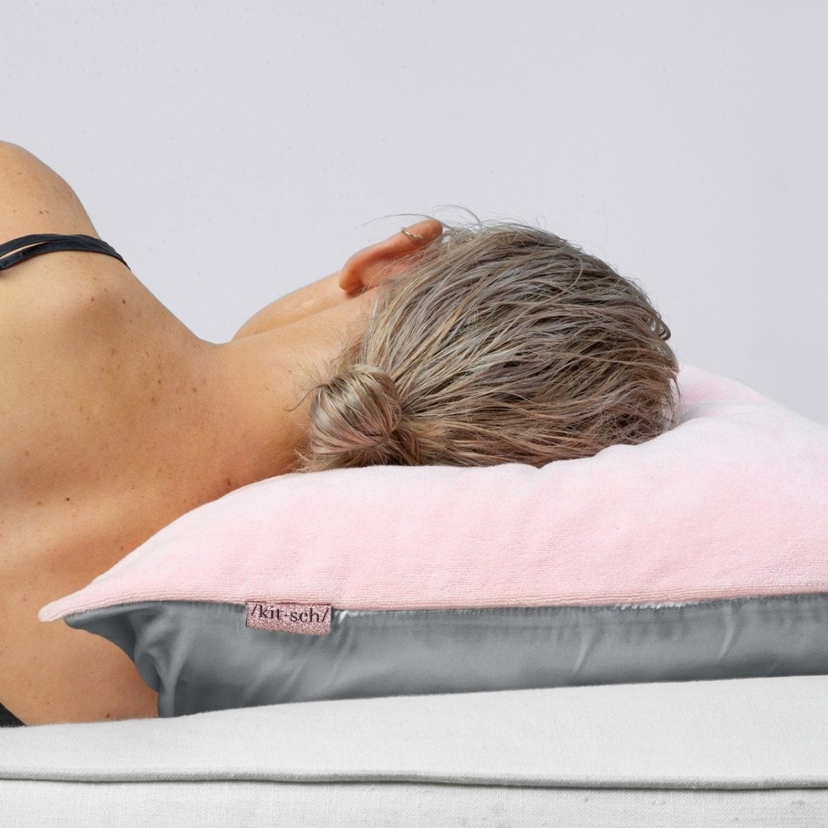 Model sleeping on a pink and grey pillowcase