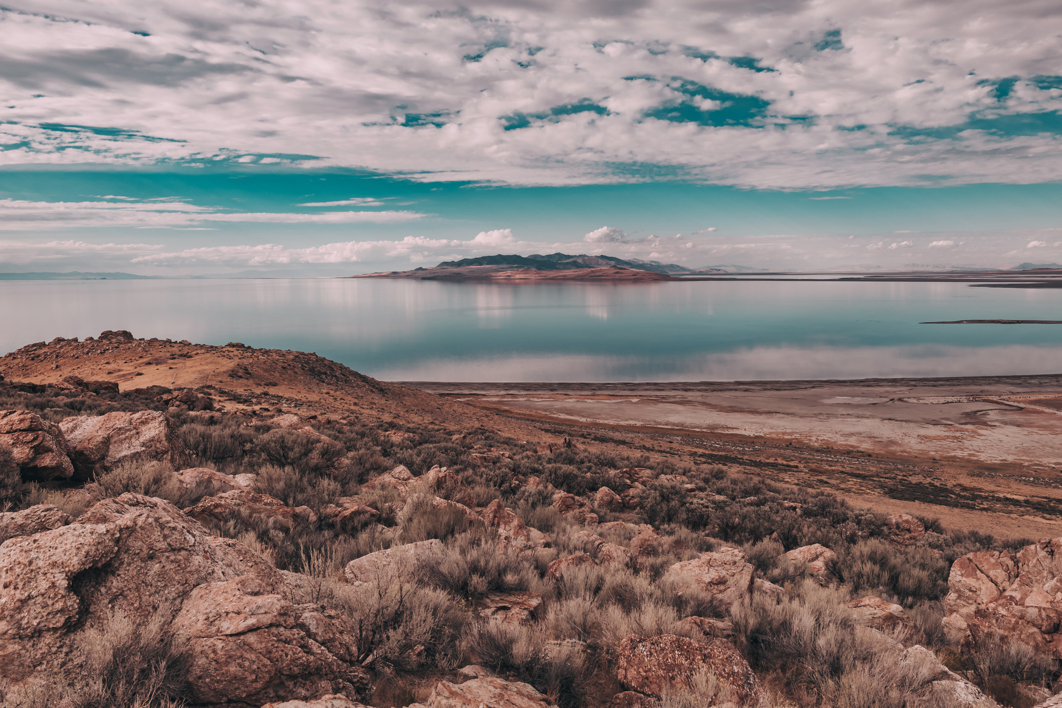Desert landscape, water reflections, dramatic clouds over great salt lake