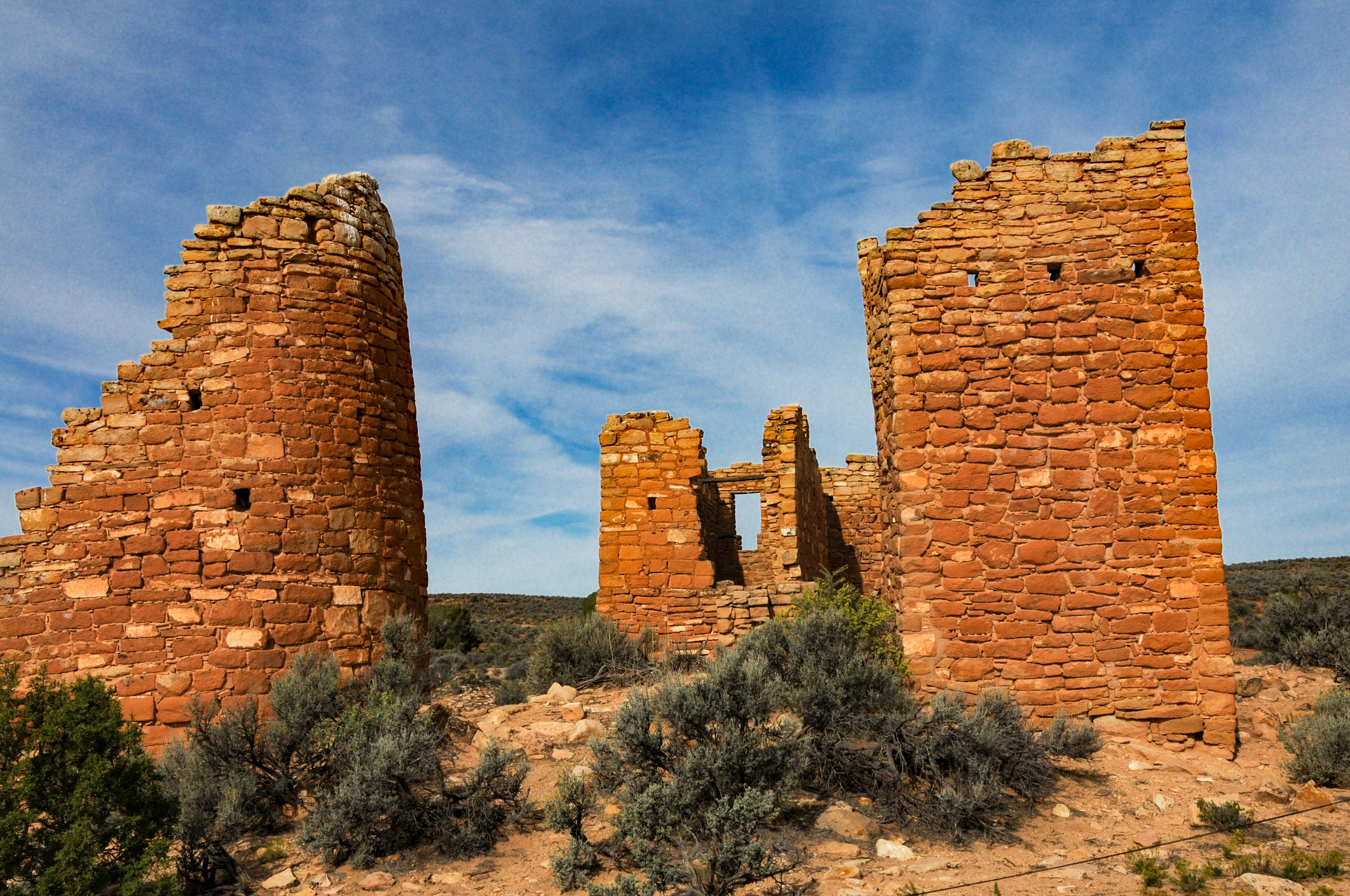 remains of ancient red brick buildings surrounded by shrub and desert landscapes