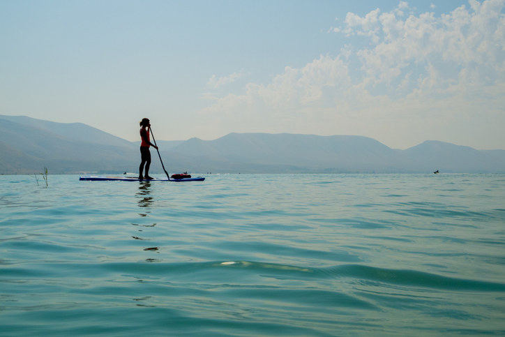 woman paddleboarding just off the North Shore beach area of the lake fairly. the blue is very blue and water calm