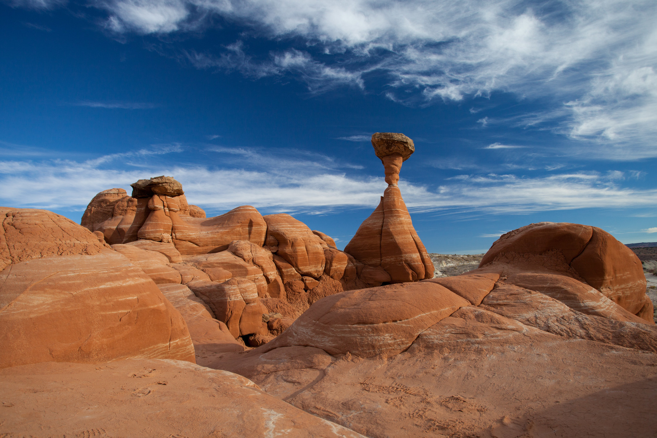 unique tall red rock formation with a rounded top, contrast against blue skies