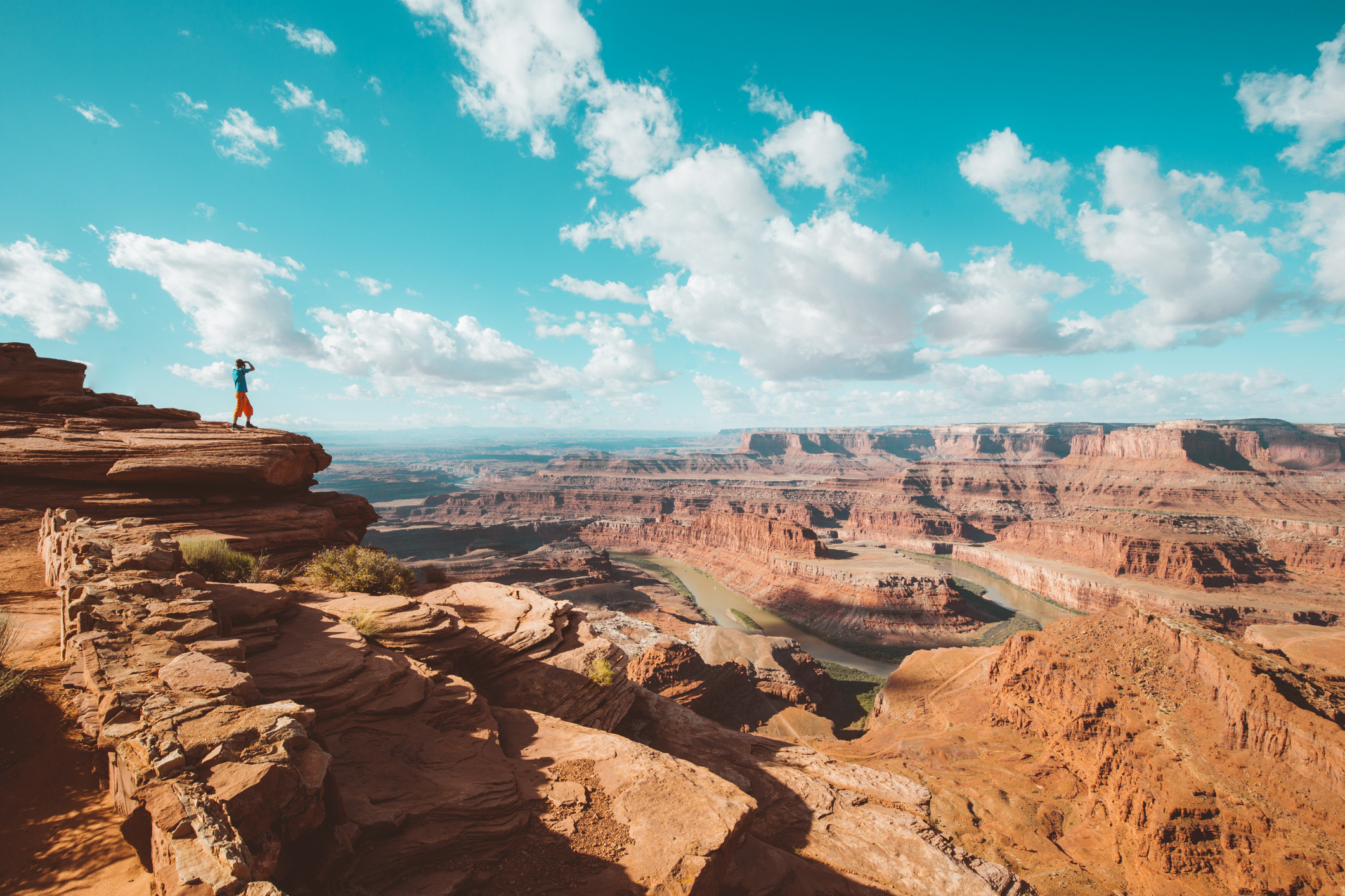 A young male hiker is standing on the edge of a cliff enjoying a dramatic overlook of the famous Colorado River and beautiful Canyonlands National Park