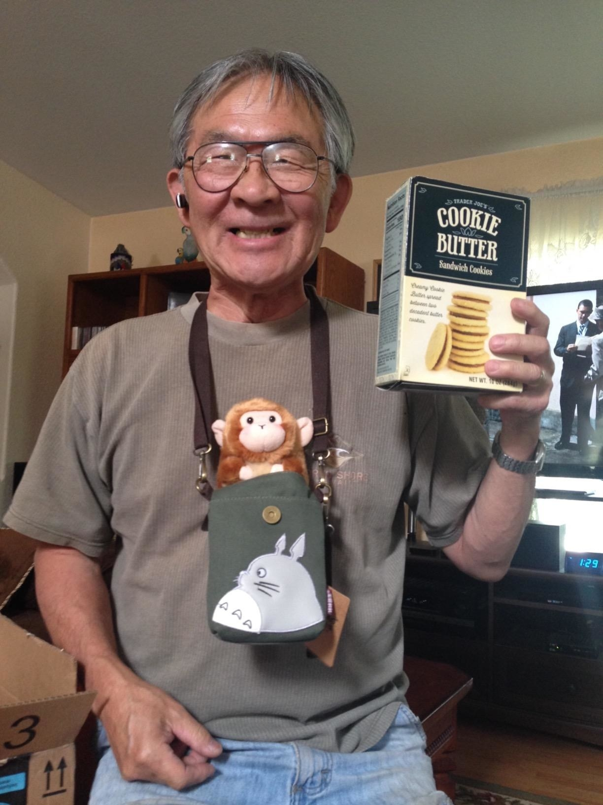 reviewer wears green canvas totoro bag with long strap around next with stuffed monkey in it and holds up box of trader joe's cookie butter sandwich cookies