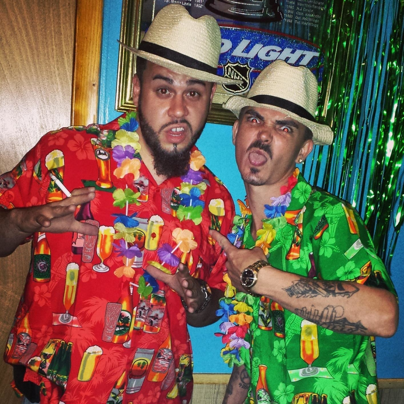 two reviewers wear matching hawaiian shirts covered in tiki drinks