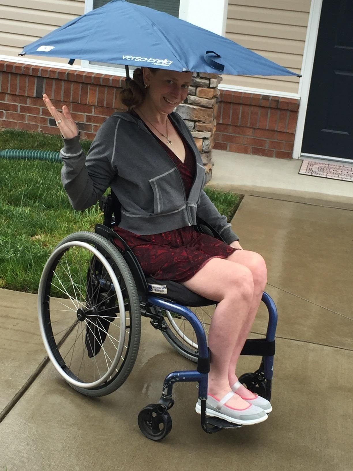 A reviewer showing off the umbrella that is clipped to their wheelchair
