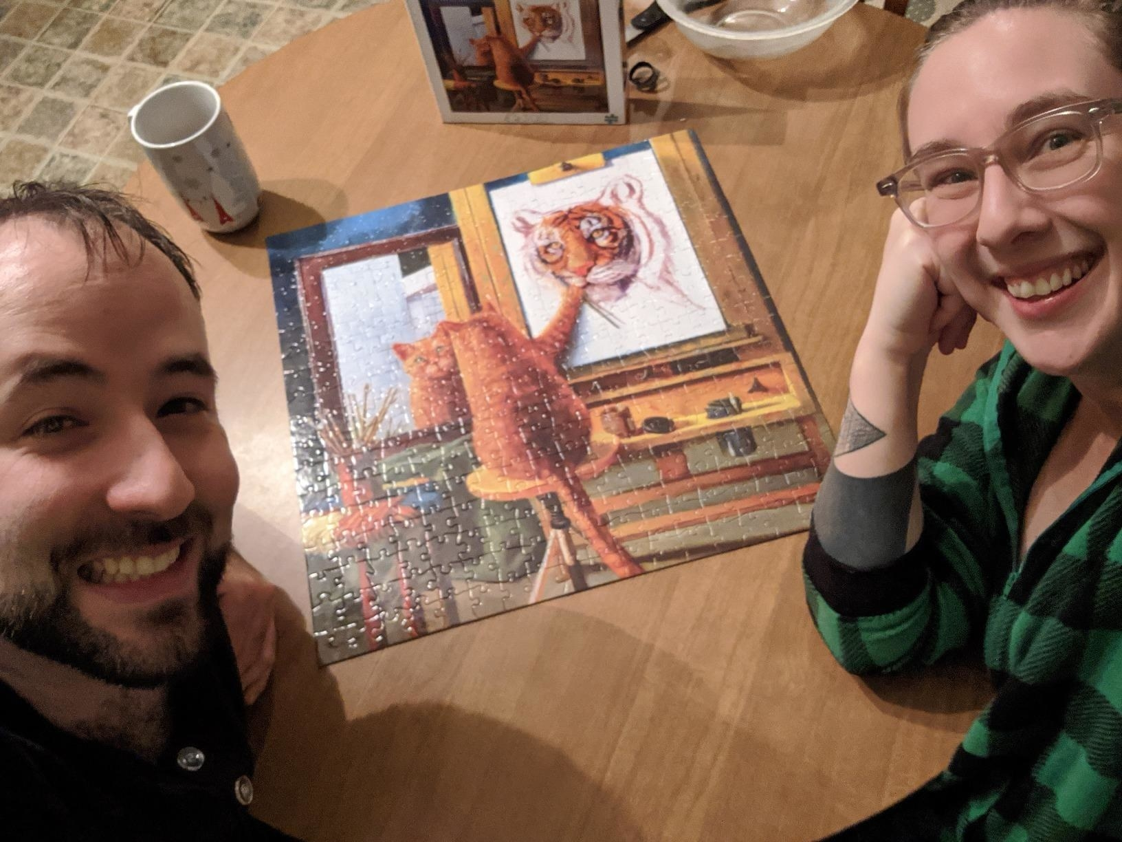 couple poses with finished puzzle that looks like Norman Rockwell's Triple Self-Portrait, except with a cat panting itself as a tiger