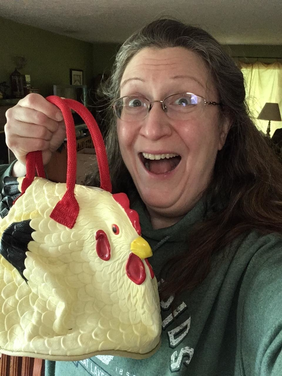 reviewer grins holds chicken purse made out of plastic or rubber