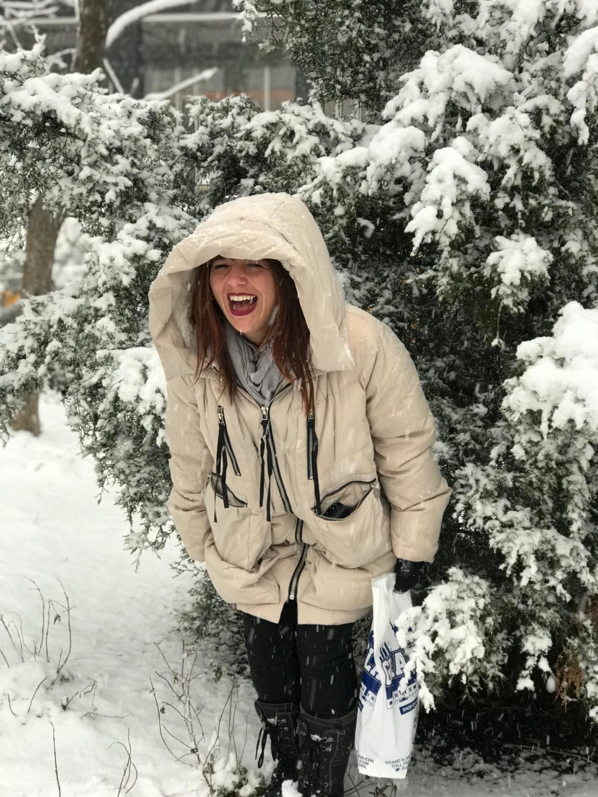 reviewer in quilted fluffy coat looks really happy in snow