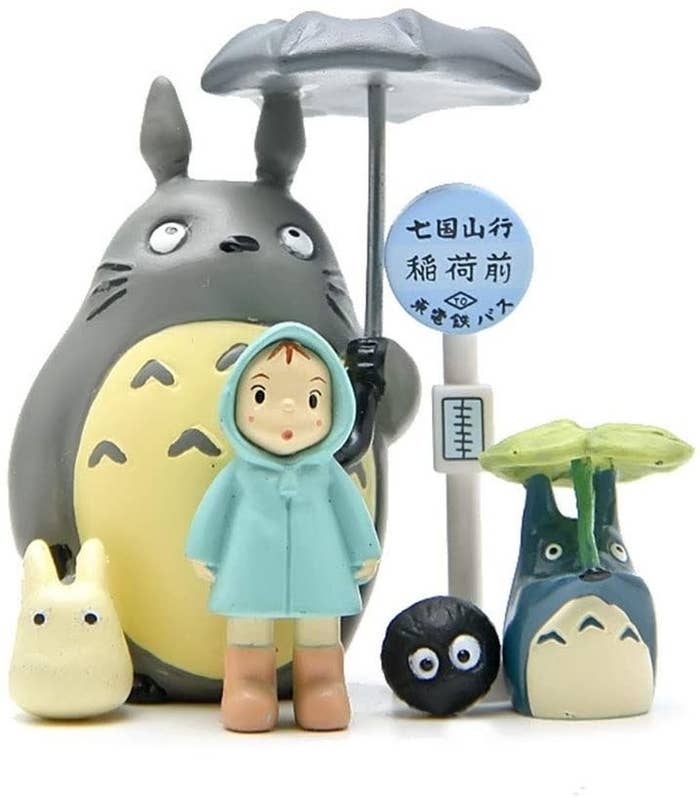 Five characters from My Neighbour Totoro next to a bus stop sign