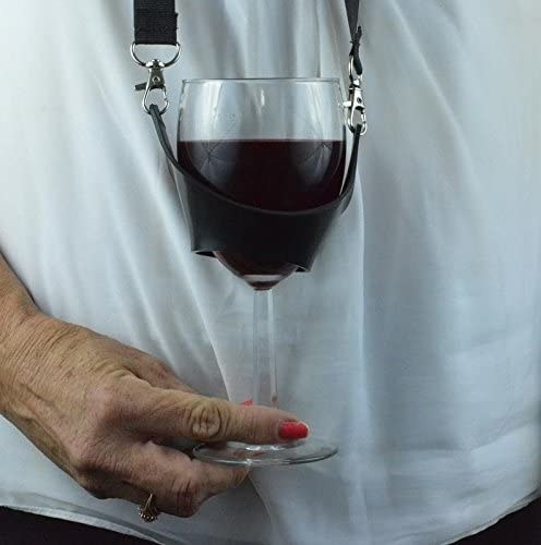 A wine glass sits in a holder lopped around a person's neck