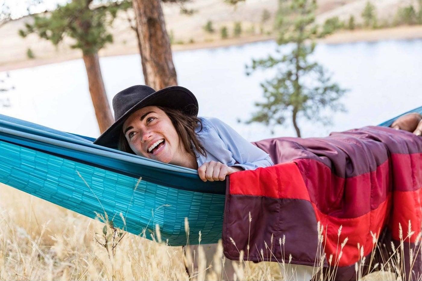 a model laying in a blue hammock