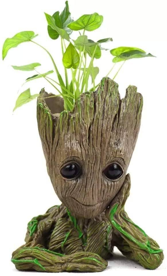 Groot rests his cheek on his hand with plants coming out of his skull