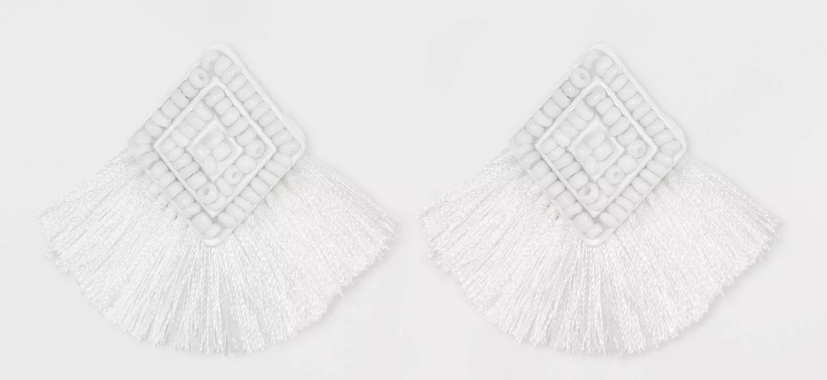A pair of diamond shaped beaded white earrings with fringe on the bottom