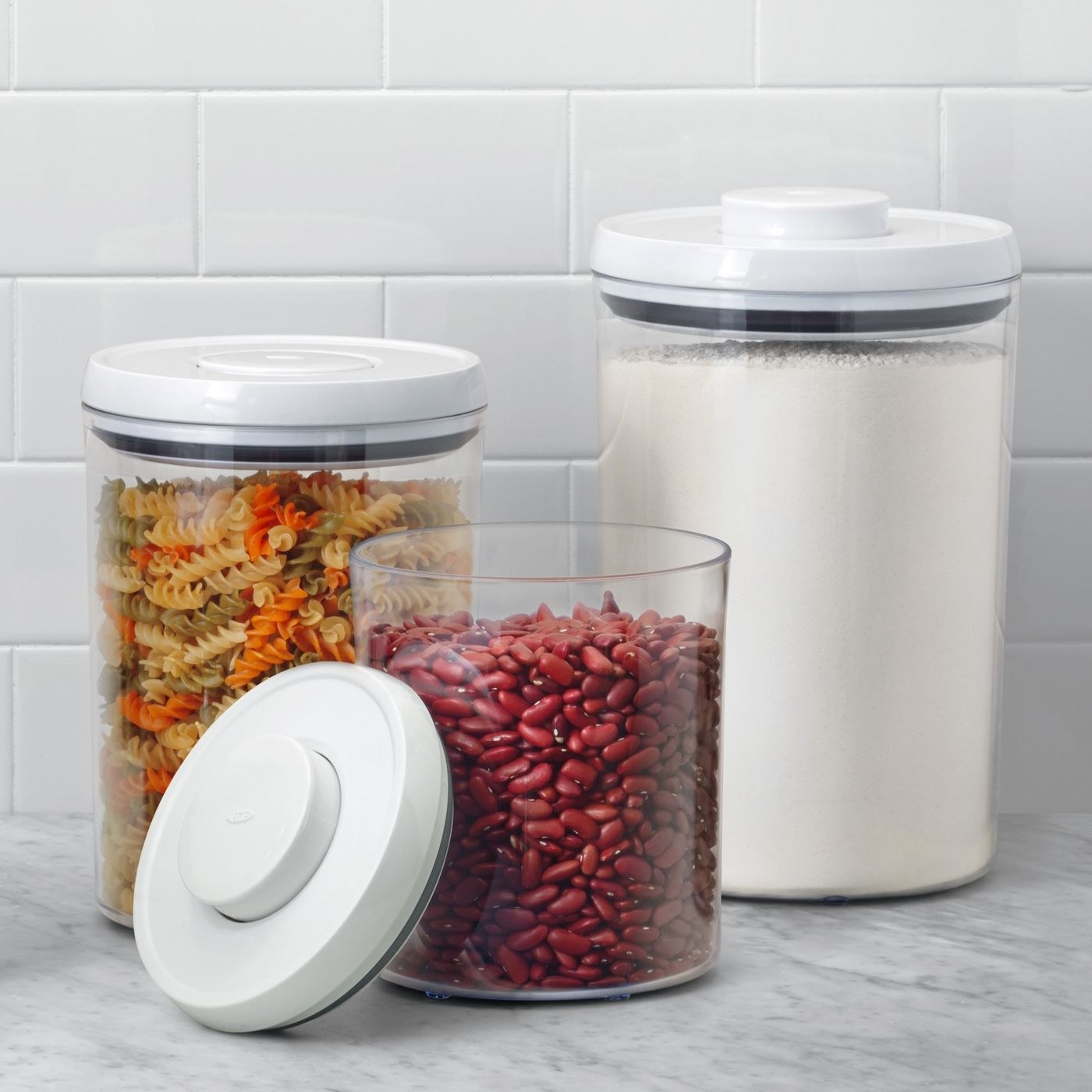 three clear circular containers with pop-seal white lids