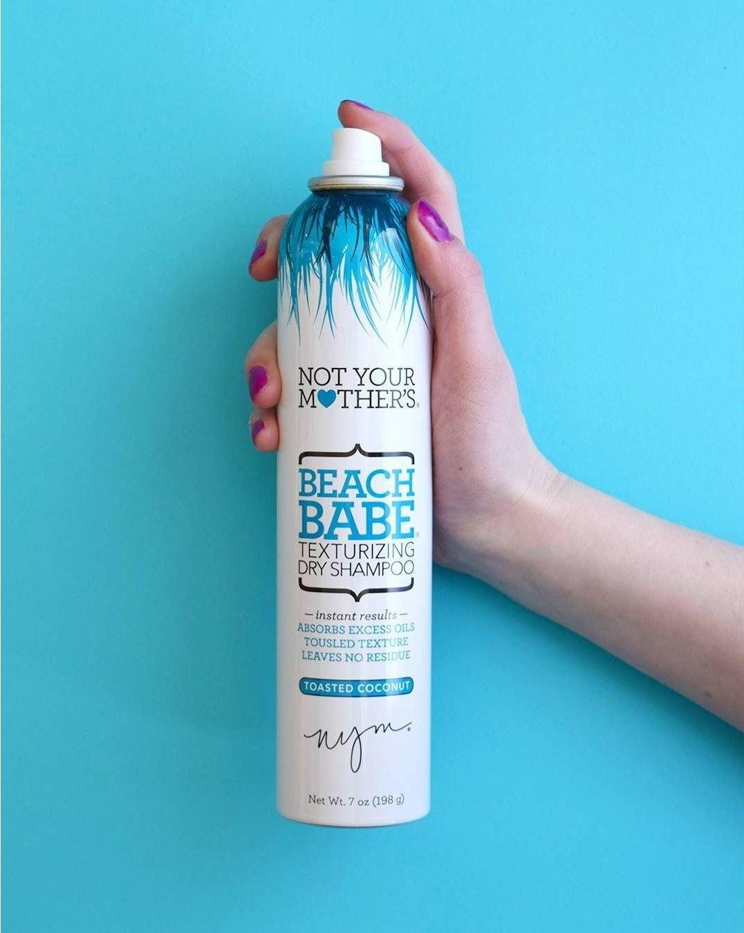 a model holding a spray bottle of beach baby texturizing spray