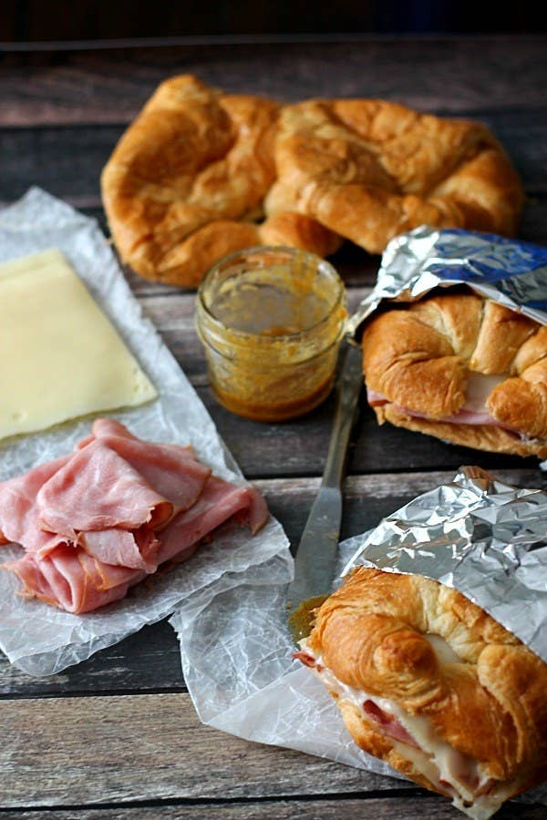 Ham, cheese, and honey mustard on a picnic bench, alongside two pre-made croissant sandwiches.