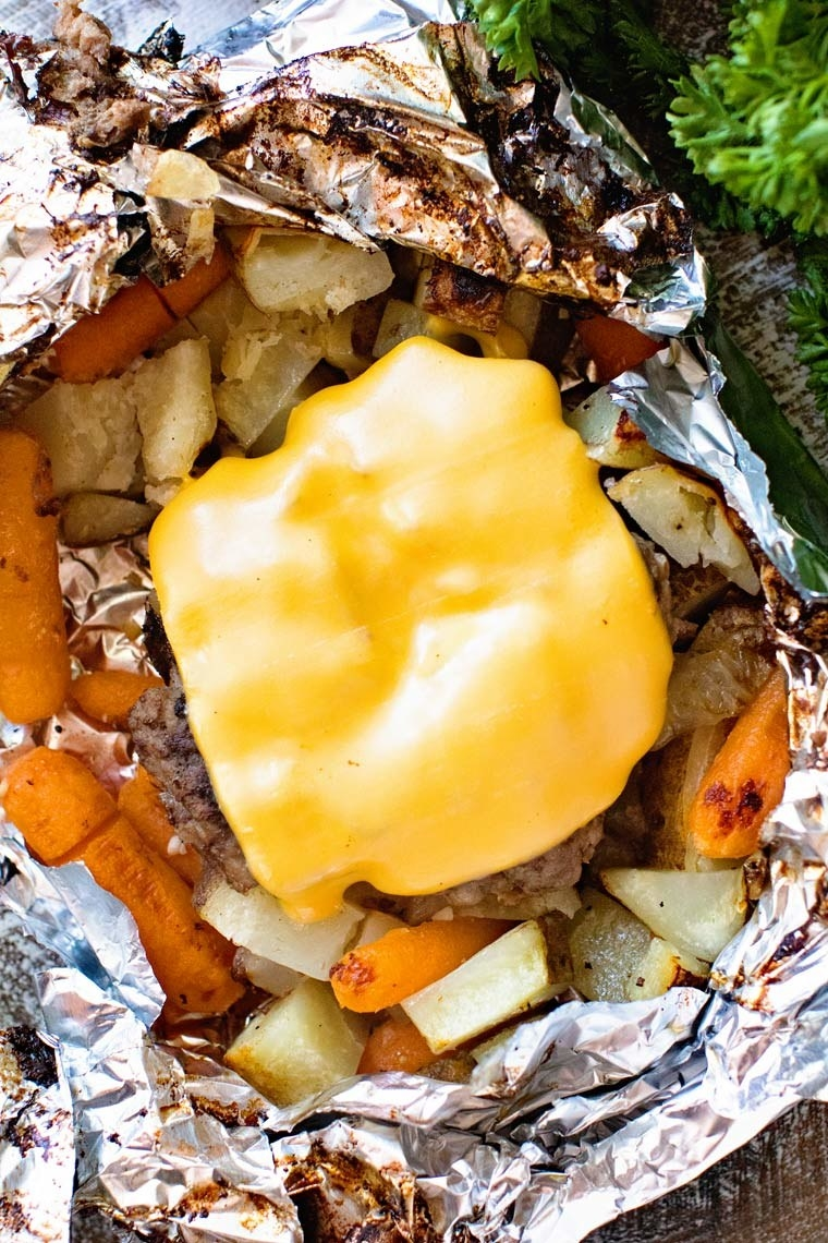 A cheeseburger on top of cooked potatoes and carrots in a foil pack.