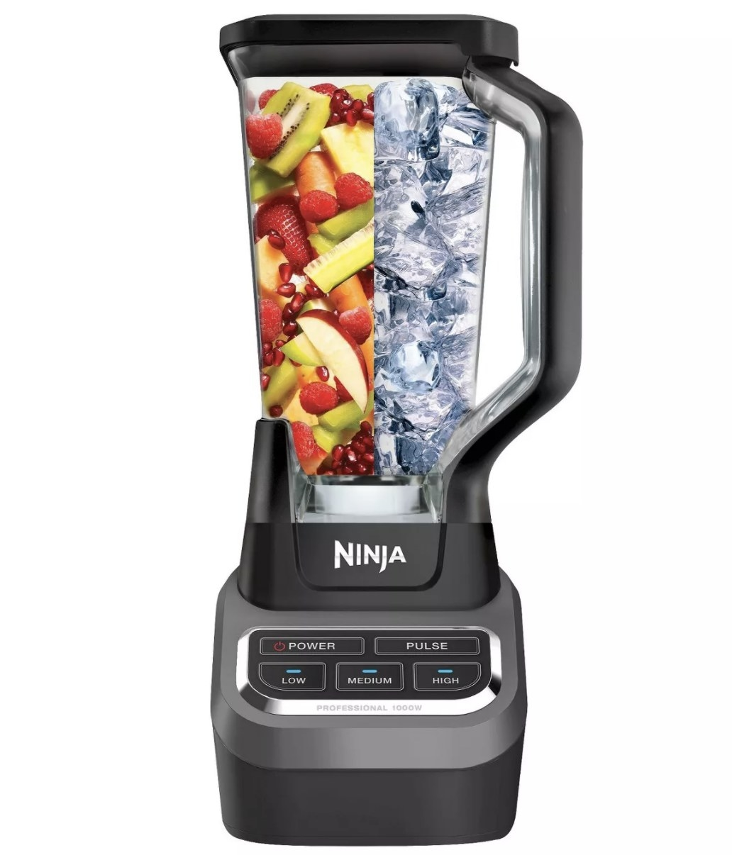 A blender with fruit and ice in it