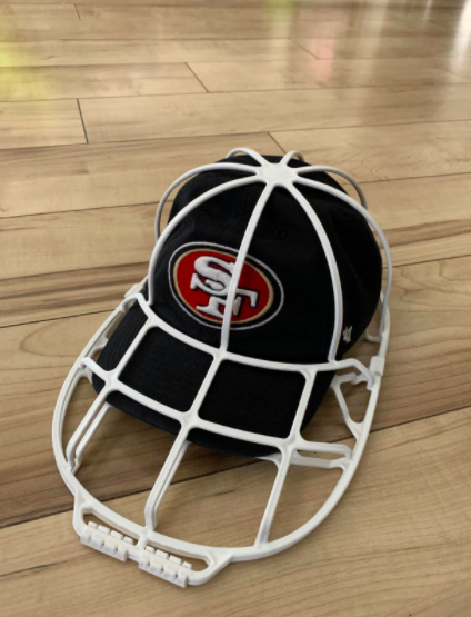 A reviewer photo of the white plastic cage, which is shaped like an oversized baseball cap, with a cap inside