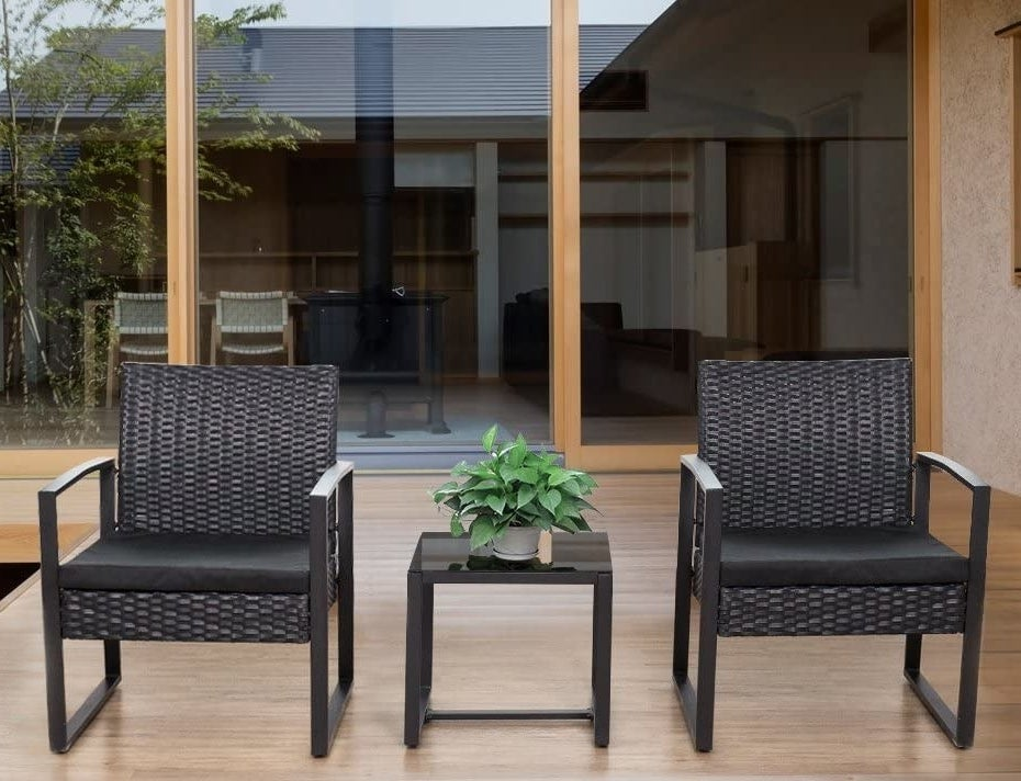 two modern black wicker chairs and small table