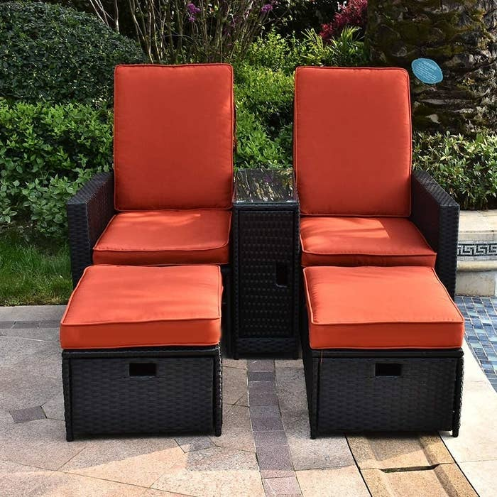 high-back chairs with ottomans with bright orange cushions