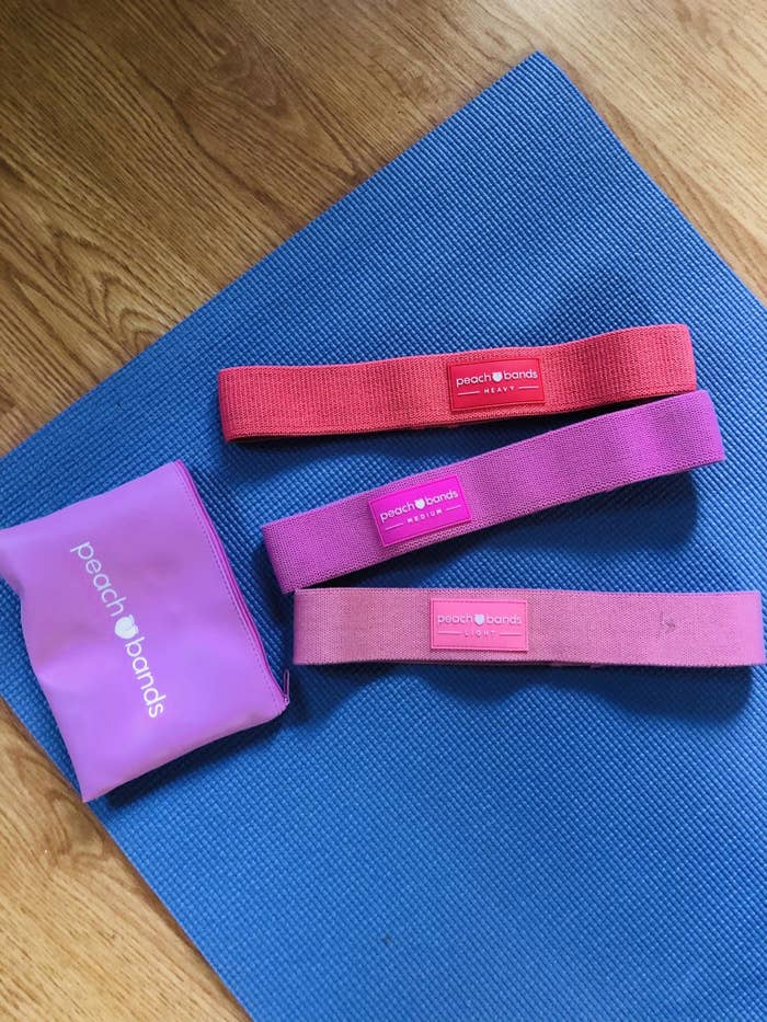The set of three peach bands lying on a workout mat