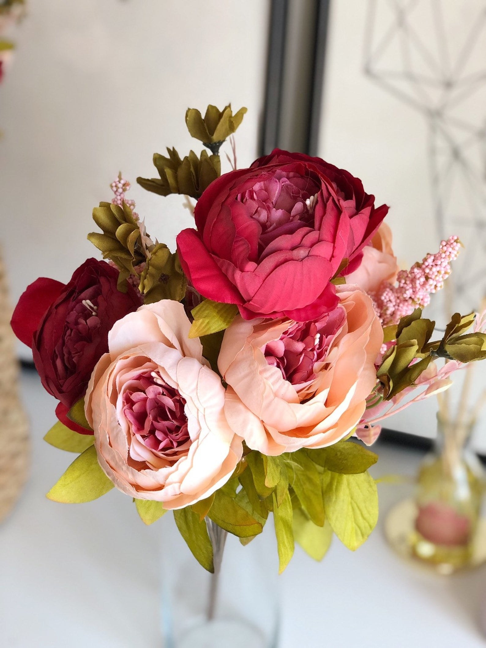 A bouquet of fake peonies in peach and red with green leaves