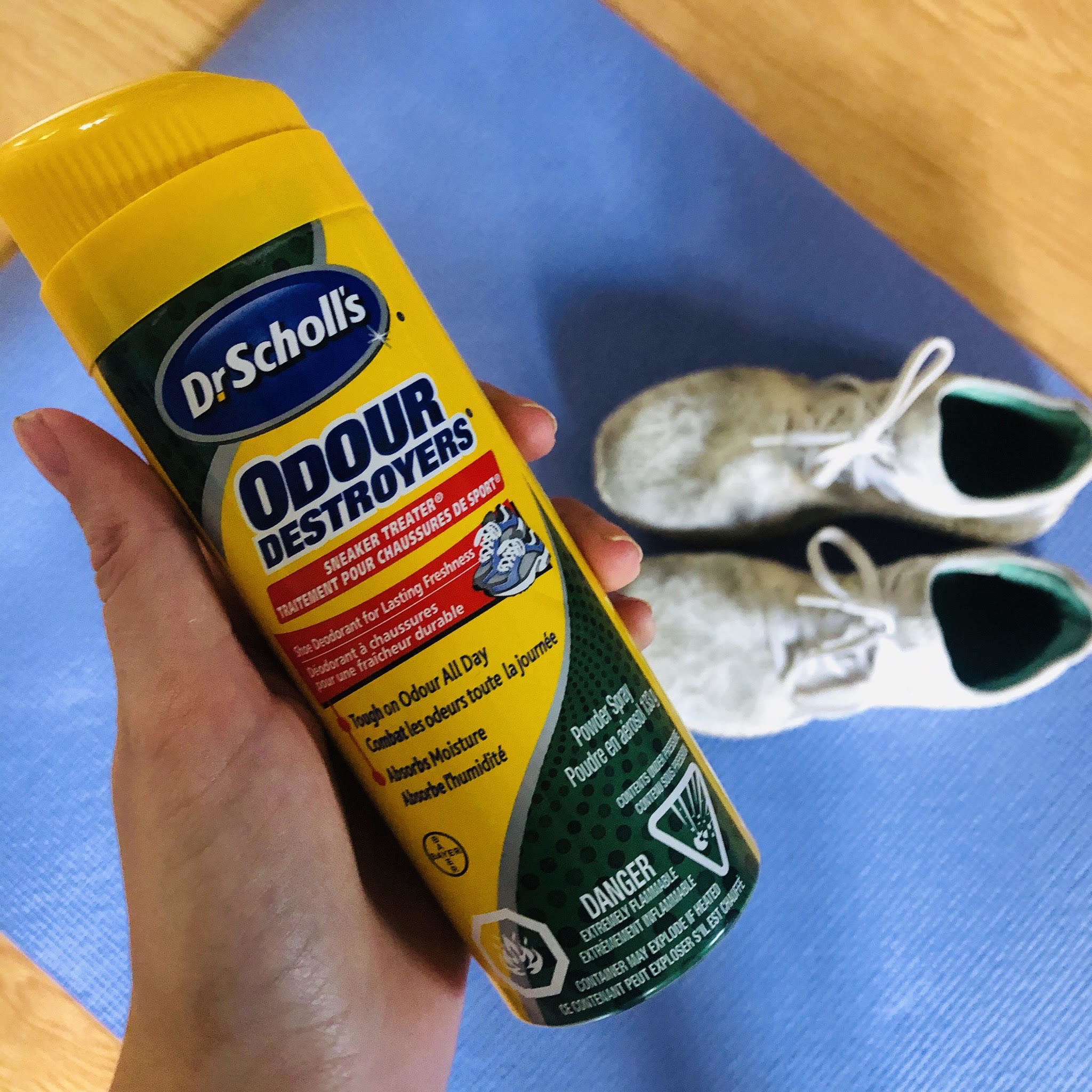 A bottle of the sneaker spray, with a pair of un-stinky sneakers in the background