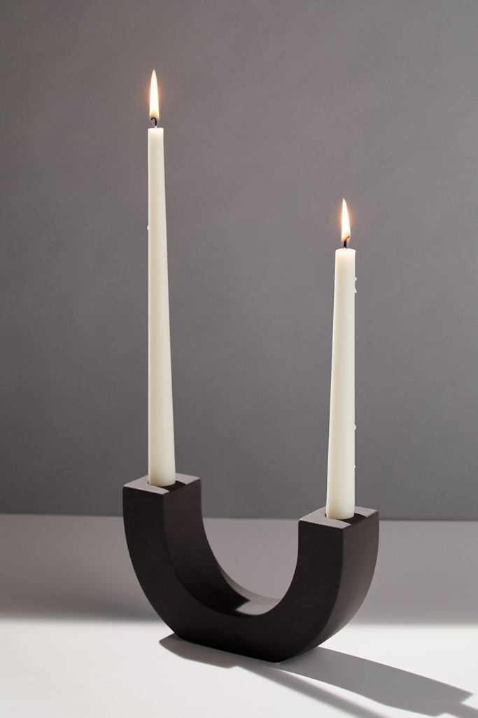 A ceramic u-shaped holder in black with two long candlesticks in either whole
